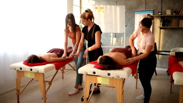 vidéos et rushes de masseuse observant ses élèves à un examen de massage pratique - banc de massage