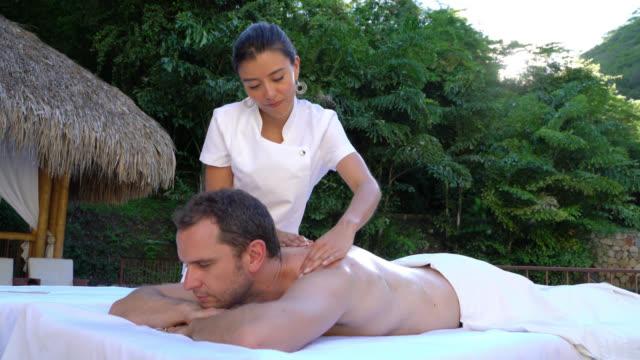 Masseuse working at an outdoor spa massaging a customer