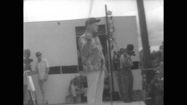massive crowd of american servicemen stand and sit watching bob hope perform on stage during christmas uso tour in south vietnam / hope tells jokes... - ミス・ワールド点の映像素材/bロール