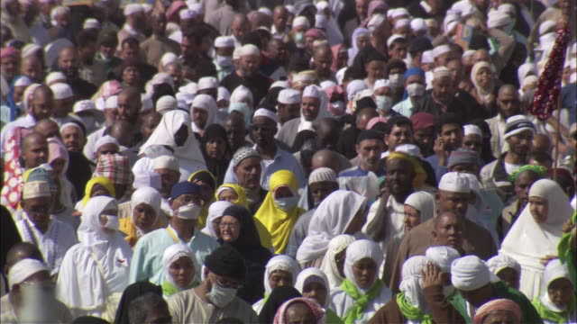 A massive crowd of Muslims surges along a wide road in Saudi Arabia.