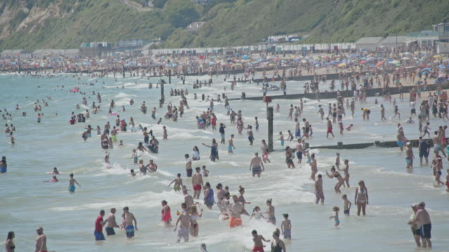 massive crowds enter the water on bournemouth beach on may 31 2020 in bournemouth england the deputy chief medical officer of england fears the uk is... - semi dress stock videos & royalty-free footage