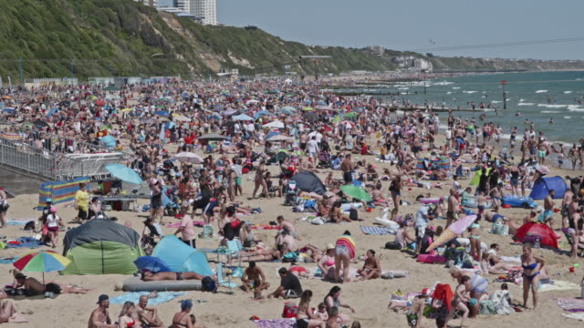 massive crowds gather on bournemouth beaches making social distancing very difficult on may 31, 2020 in bournemouth, england. the british government... - イングランド南西部点の映像素材/bロール