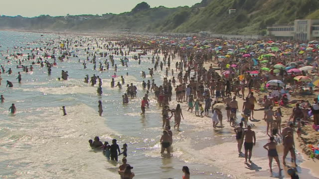 massive crowds on bournemouth beach after coronavirus lockdown restrictions were eased - busy stock videos & royalty-free footage