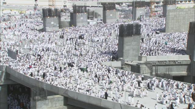 Massive crowds surge across an elevated structure in Mecca, Saudi Arabia.