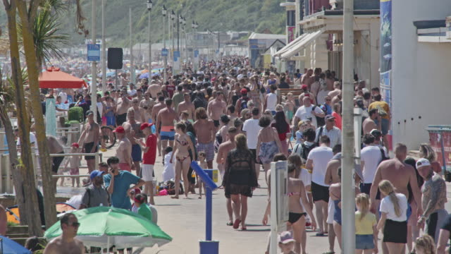 massive crowds walk along west undercliff promenade next to bournemouth beach the overcrowding makes it hard to social distance on may 31 2020 in... - semi dress stock videos & royalty-free footage