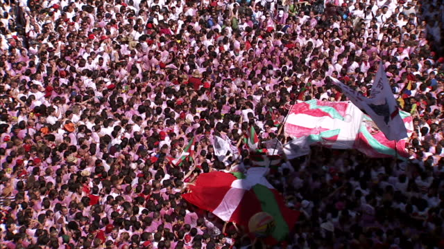 massive, dense unidentifiable crowd moving in wave like motion, holding up basque flags & hitting beach balls outside of the town hall of pamplona.... - ビーチボール点の映像素材/bロール