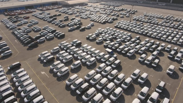vídeos de stock e filmes b-roll de massive dockside yard of new cars for import/export with morning sunrise, aerial view - aluguer de automóveis