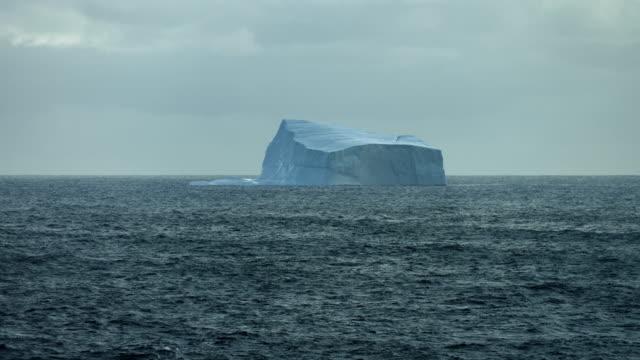 massive iceberg on choppy arctic waters - northwest passage stock videos and b-roll footage