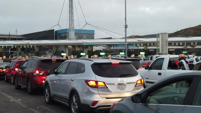 massive lines of cars waiting to cross into the united states from mexico at the san ysidro international crossing in tijuana - geographical border stock videos & royalty-free footage