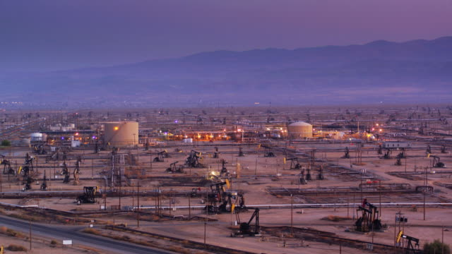massive oil field with illuminated refinery at sunset - drone shot - oil refinery stock videos & royalty-free footage