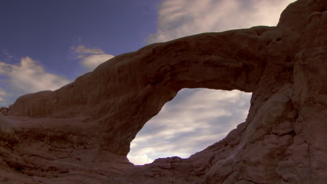 massive sandstone arch with clouds racing past behind it - arch stock videos & royalty-free footage