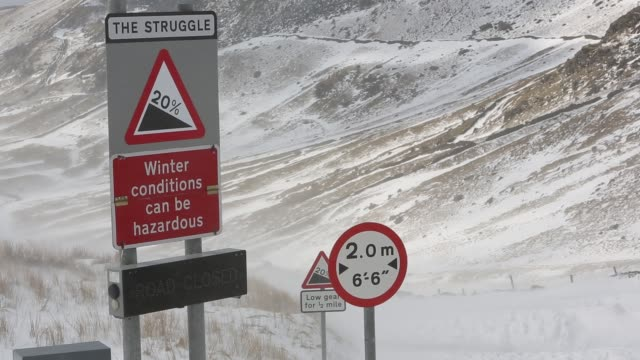 massive snow drifts block the kirkstone pass road above ambleside in the lake district, uk during the extreme weather event of late march 2013. shot taken on 25th march 2013. - road closed sign stock videos & royalty-free footage