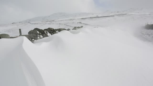 Massive snow drifts block the Kirkstone Pass road above Ambleside in the Lake District, UK during the extreme weather event of late March 2013. shot taken on 25th March 2013.