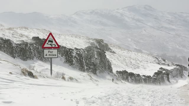 massive snow drifts block the kirkstone pass road above ambleside in the lake district, uk during the extreme weather event of late march 2013. shot taken on 25th march 2013. - steep stock videos & royalty-free footage