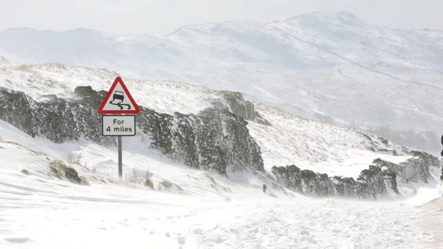 massive snow drifts block the kirkstone pass road  - road closed sign stock videos & royalty-free footage
