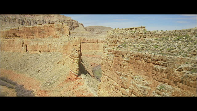 aerial a massive wall of rock upthrust from high plains desert, with vegetation on the wall's top and sloping end - formato panoramico con bande nere video stock e b–roll