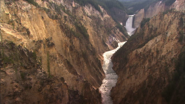 A massive waterfall pours into a gorge where a white water river flows through Yellowstone National Park.