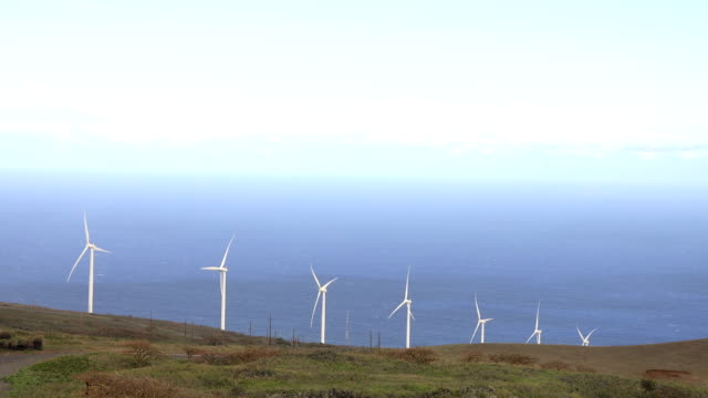 massive wind turbines working on egde of maui island - butte rocky outcrop stock videos & royalty-free footage