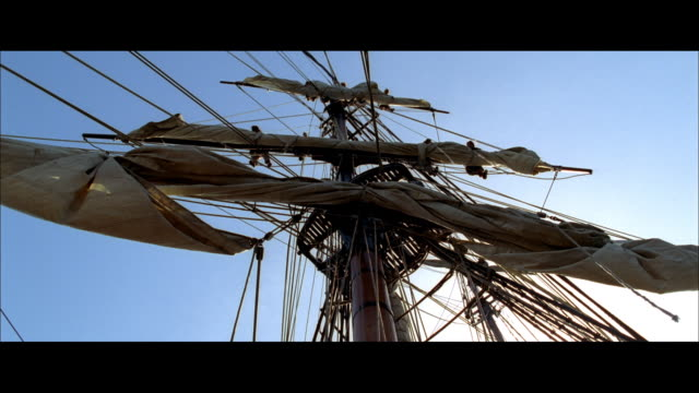 la mast of a sailing ship with furled sails and rigging, and sails being unfurled and sheeted home - rigging nautical stock videos & royalty-free footage