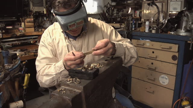 MS Master jeweler inspecting gold watch band in his workshop / Morton Grove, Illinois, USA