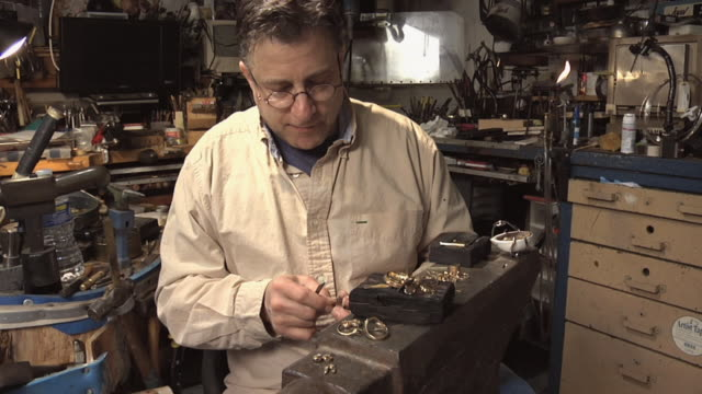 MS Master jeweler inspecting old jewelry pieces and preparing them for salvage in his workshop / Morton Grove, Illinois, USA