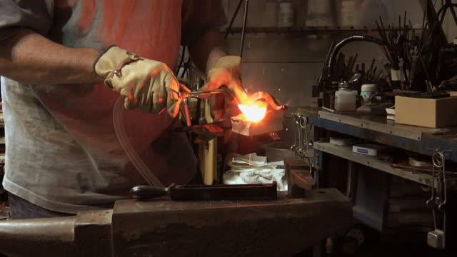 vídeos de stock, filmes e b-roll de zi cu master jeweler melting and forging pure gold to make jewelry in his workshop / morton grove, illinois, usa - fundir técnica de vídeo