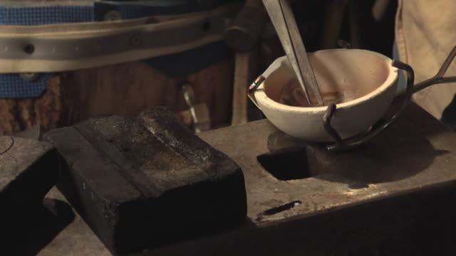 vídeos de stock, filmes e b-roll de cu master jeweler removing hot gold droplet made from melted jewelry pieces in his workshop / morton grove, illinois, usa - fundir técnica de vídeo