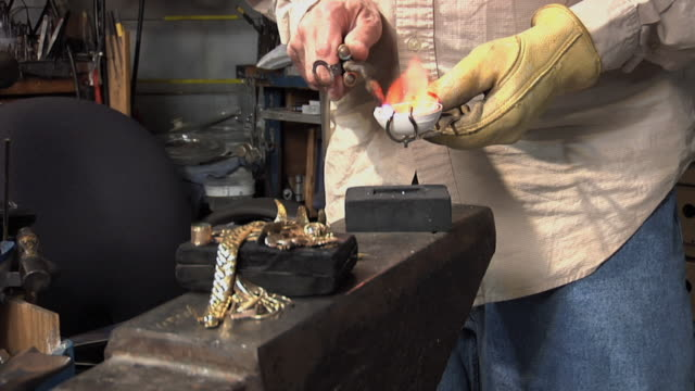 CU Master jeweler using blowtorch to melt old jewelry pieces / Morton Grove, Illinois, USA