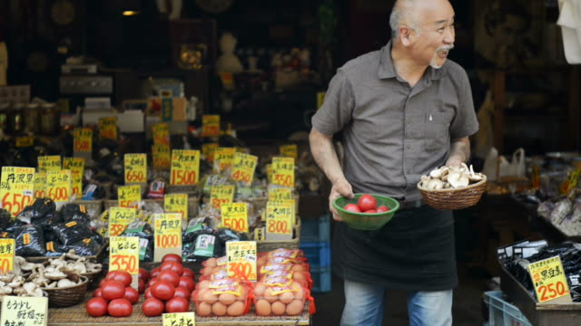 ms pan master of greengrocer is salesperson standing in front of shop / toyooka, hyogo, japan - 売る点の映像素材/bロール