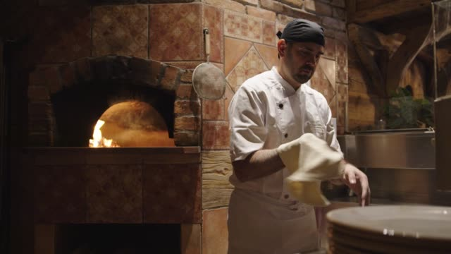 vidéos et rushes de maître pizzeria jetant la pâte à pizza en l'air - fraîcheur