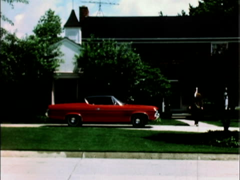 Matador hardtop pulling into suburban circular driveway businessman walks out to car / MS car's red interior businessman gets into his friend's car /...