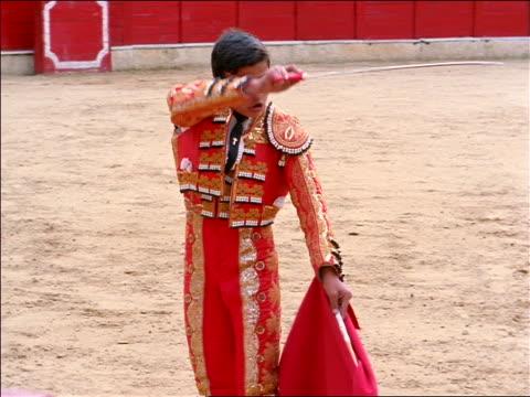 Matador raising sword + cape / steps aside as bull charges through cape / Bogota, Colombia