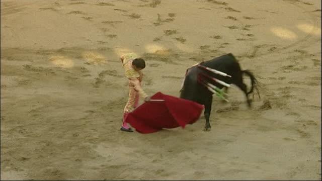 matador waving red flag and bull charging at him at bullfighting event in catalonia spain - bull animal stock videos & royalty-free footage