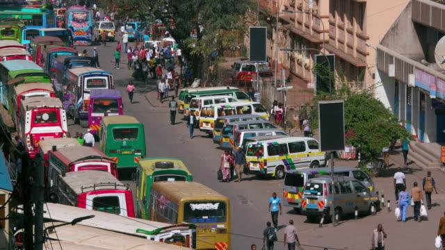 matatus at thika town stage bus station ronald ngala street, nairobi, kenya, africa - ナイロビ点の映像素材/bロール