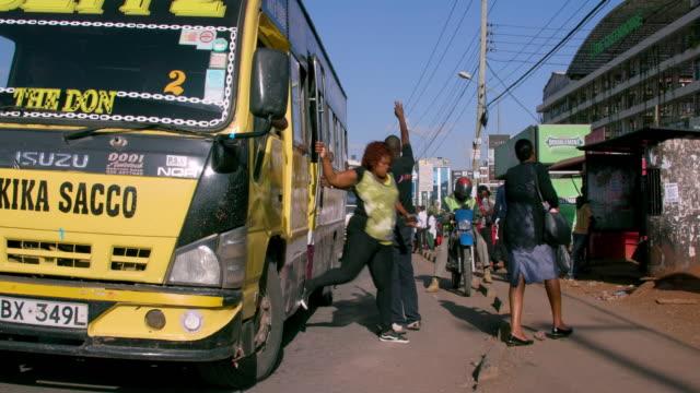 matatus drops passengers at bus stop ngong road, nairobi, kenya, africa - 降り立つ点の映像素材/bロール
