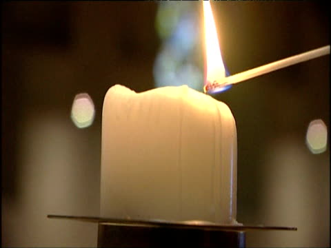 match descends to light white candle in church - candle stock videos & royalty-free footage