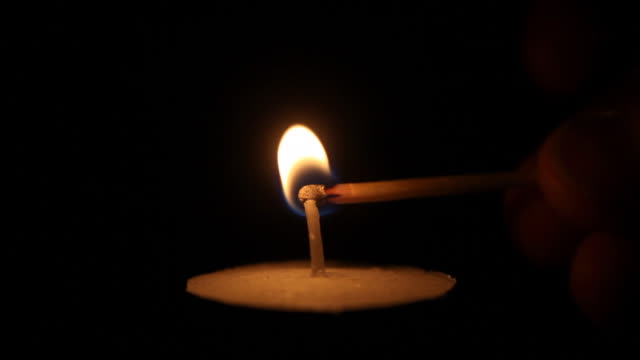 match igniting tea light candle - igniting stock videos & royalty-free footage