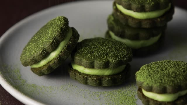 matcha green tea cream sandwich cookies served in a plate. - sprinkling stock videos & royalty-free footage