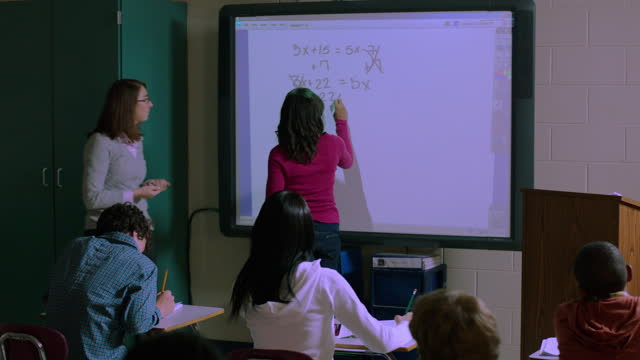 a math teacher congratulates her student on successfully completing an equation. - interactive whiteboard stock videos & royalty-free footage