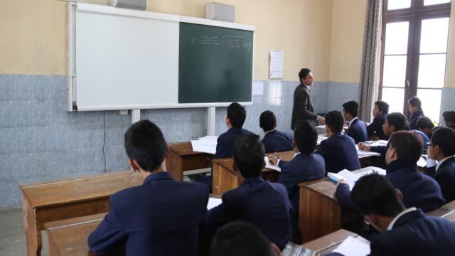math teacher explains a subject to a class full of students - christian ender stock-videos und b-roll-filmmaterial