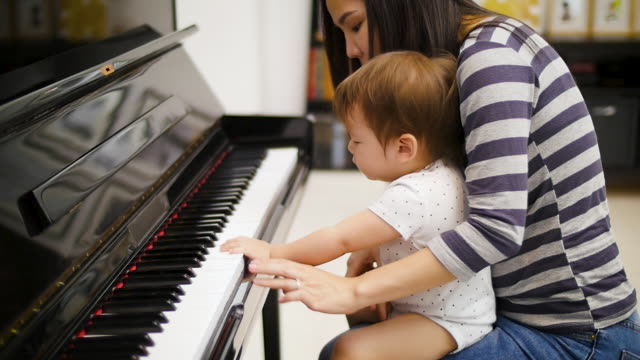 vídeos de stock e filmes b-roll de mather and little baby boy playing piano at home, family spending time together concept - piano