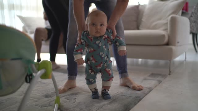 mather helping son learn to walk at home - beginnings stock videos & royalty-free footage