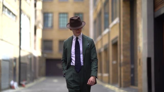 Mathias Lefevre wears a hat a green suit blazer jacket a shirt a blue tie brown shoes during London Fashion Week Men's June 2018 on June 09 2018 in...