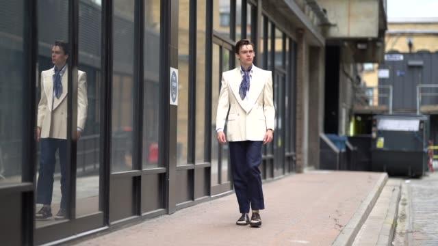 Mathias Lefevre wears a white blazer jacket a blue scarf blue pants sandals a shirt during London Fashion Week Men's June 2019 on June 09 2019 in...