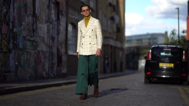 mathias lefevre wears sunglasses a yellow turtleneck top a white checked blazer jacket green flare pants brown shoes during london fashion week men's... - pants stock videos & royalty-free footage