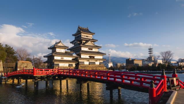 vídeos de stock, filmes e b-roll de matsumoto castle and famous red wooden bridge timelapse - nagano