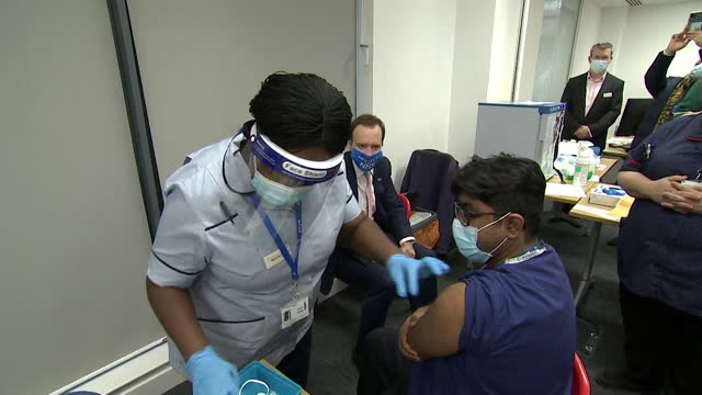 matt hancock, health secretary, watches nhs staff, get covid-19 vaccine at milton keynes hospital, on first day of vaccine roll out - first occurrence stock videos & royalty-free footage