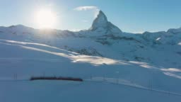 Matterhorn Mountain, Gornergrat Train and Sun in Winter at Sunset. Switzerland. Aerial View