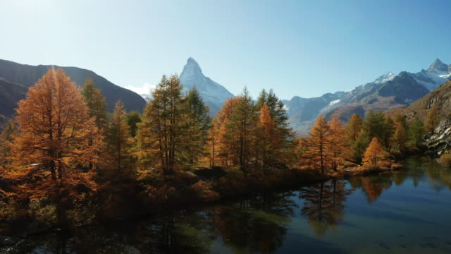 matterhorn peak with golden larches and grindjisee lake in zermatt, switzerland. - outdoor pursuit stock videos & royalty-free footage