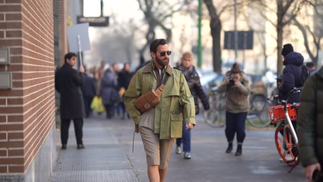 matthew zorpas wears sunglasses, a brown leather fanny pack shoulder strapped fendi bag, a green jacket, a brown shirt, shorts, fendi shoes, outside... - milan fashion week stock videos & royalty-free footage